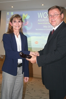 Dr. Rebecca Lochmann, incoming president of the World Aquaculture Society, is passed the gavel by Graham Mair, outgoing president, during the society's conference held in May in Jeju, South Korea. More than 2000 of the world's leading aquaculture scientists, industry leaders and producers attended the event.
