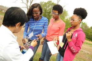 Dr. Shaheen Khan (bottom left), a chemistry lab instructor at UAPB conducts an experiment on exothermic chemistry with Kintress Watson, Ray-Ven Nelson, and Shanise Davis during the 2015 Girls in STEM Conference.